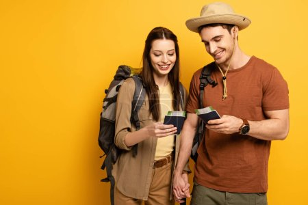 Photo pour Couple of happy travelers with backpacks holding passports and tickets on yellow - image libre de droit