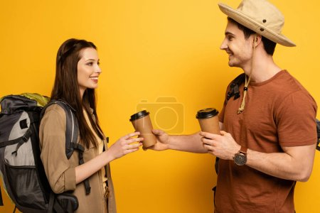 Photo for Couple of happy travelers with backpacks holding coffee to go on yellow - Royalty Free Image
