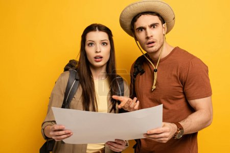 Photo for Couple of confused tourists with backpacks looking at map  on yellow - Royalty Free Image