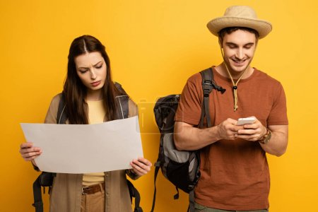 Photo for Couple of happy tourists with backpacks looking at map and smartphone on yellow - Royalty Free Image