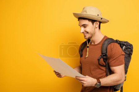 Photo pour Handsome smiling tourist in hat with backpack looking at map on yellow - image libre de droit