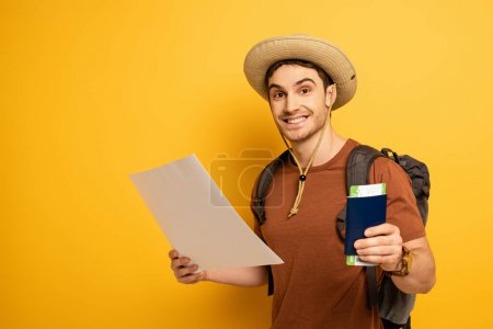 Photo for Smiling tourist in hat with backpack holding passport, ticket and map on yellow - Royalty Free Image