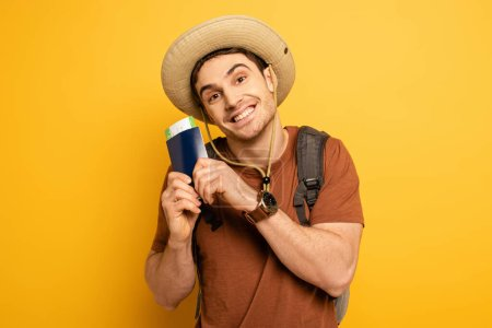 Photo pour Emotional tourist in hat with backpack holding passport and ticket on yellow - image libre de droit