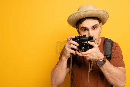 Photo pour Beau touriste en chapeau avec sac à dos prenant des photos à l'appareil photo sur jaune - image libre de droit