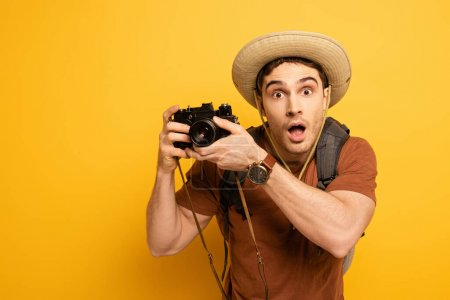 Photo for Shocked tourist in hat with backpack holding photo camera on yellow - Royalty Free Image
