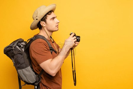 handsome traveler in hat with backpack holding photo camera on yellow