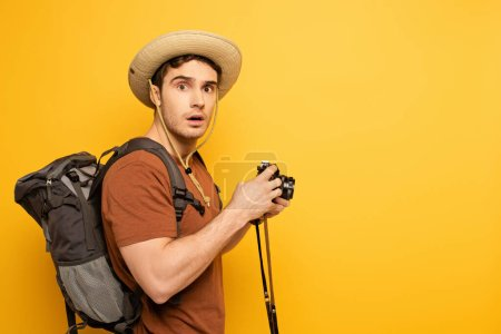 Photo for Shocked traveler in hat with backpack holding photo camera on yellow - Royalty Free Image