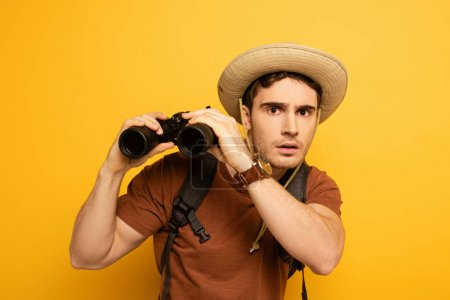 Photo pour Surprised traveler in hat with backpack holding binoculars on yellow - image libre de droit
