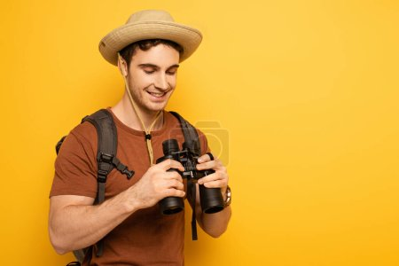 Photo pour Handsome smiling traveler in hat with backpack holding binoculars on yellow - image libre de droit