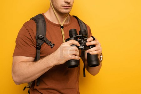 Photo pour Cropped view of traveler with backpack holding binoculars on yellow - image libre de droit