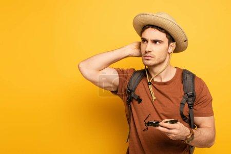Photo pour Handsome pensive traveler holding compass on yellow - image libre de droit