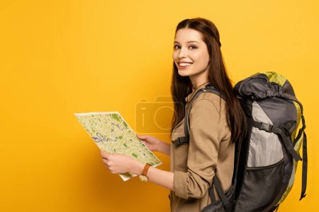 Photo for Smiling female tourist with backpack holding map on yellow - Royalty Free Image