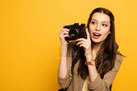 Photo for Surprised female tourist with backpack holding photo camera on yellow - Royalty Free Image