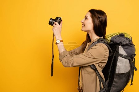 Photo for Excited tourist with backpack holding photo camera on yellow - Royalty Free Image