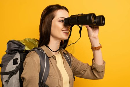 Photo for Beautiful female traveler with backpack looking through binoculars, isolated on yellow - Royalty Free Image