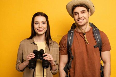 Photo pour Couple de voyageurs heureux avec sac à dos et jumelles, isolé sur jaune - image libre de droit