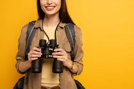 Photo pour Vue recadrée du voyageur avec sac à dos tenant des jumelles, isolé sur jaune - image libre de droit