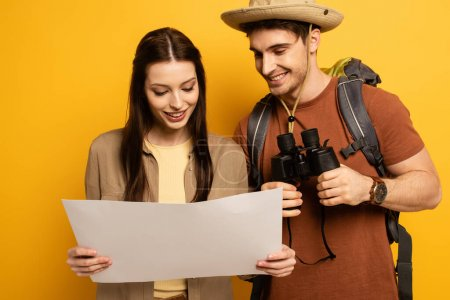Photo pour Couple of smiling travelers with backpack and binoculars looking at map on yellow - image libre de droit