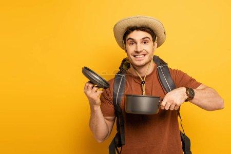 Photo pour Handsome smiling traveler holding pot on yellow - image libre de droit
