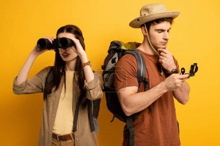 Photo pour Couple de touristes avec sacs à dos et jumelles regardant boussole sur jaune - image libre de droit