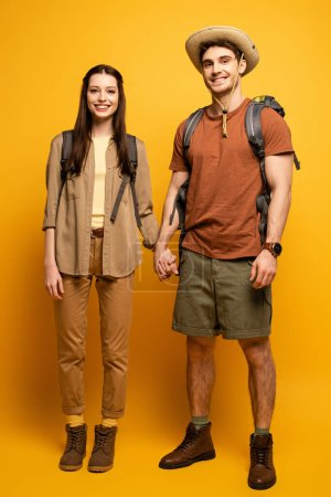 couple of happy tourists with backpacks holding hands on yellow