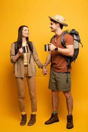 couple of happy tourists with backpacks and cups of coffee holding hands on yellow