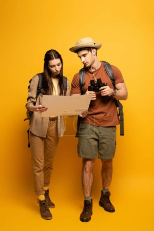 Photo for Couple of tourists with backpacks and binoculars looking at map on yellow - Royalty Free Image