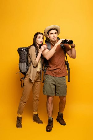 couple of emotional tourists with backpacks and binoculars on yellow