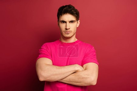 Photo pour Portrait of serious man with crossed arms in pink t-shirt on red - image libre de droit