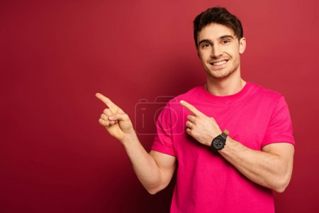 Photo for Portrait of smiling man in pink t-shirt pointing on red - Royalty Free Image