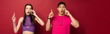 Photo pour Plan panoramique de couple choqué parlant sur les smartphones tout en pointant vers le haut sur le rouge - image libre de droit