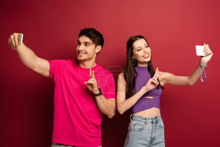 Photo for Smiling couple showing victory signs while taking selfie on smartphones on red - Royalty Free Image