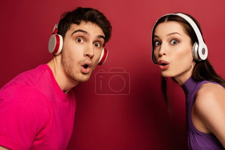 Photo pour Beau couple surpris écouter de la musique avec écouteurs sur rouge - image libre de droit