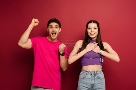 Photo for Cheerful boyfriend and happy girlfriend with hand on heart on red - Royalty Free Image