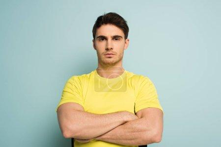 Photo pour Sportif musclé sérieux avec les bras croisés sur bleu - image libre de droit
