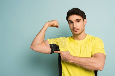 Photo for Muscular sportsman in yellow t-shirt pointing at muscles on blue - Royalty Free Image