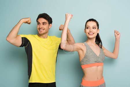 Photo for Happy athletic couple standing in sportswear showing muscles on blue - Royalty Free Image
