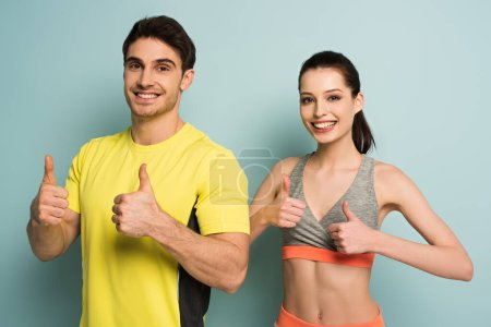 happy athletic couple standing in sportswear showing thumbs up on blue