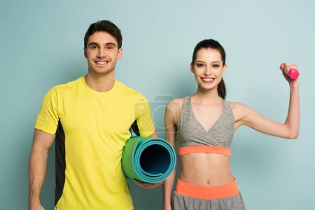 Photo for Cheerful athletic couple holding fitness mat and dumbbell on blue - Royalty Free Image