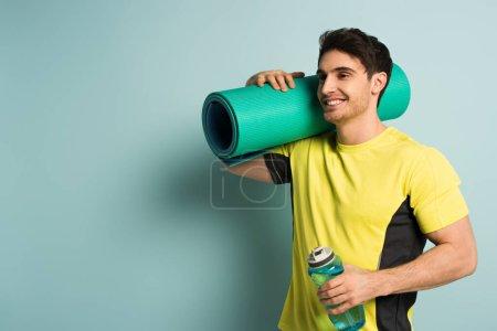 Photo pour Sportif sportif souriant en t-shirt jaune tenant tapis de fitness et bouteille de sport avec de l'eau sur bleu - image libre de droit