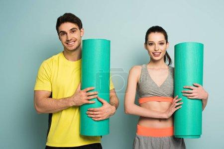 Foto de Alegre pareja atlética celebración de colchonetas de fitness en azul - Imagen libre de derechos