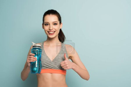 Photo for Happy athletic woman holding sports bottle with water and showing thumb up on blue - Royalty Free Image