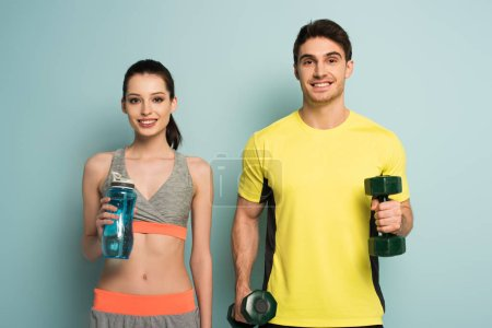 Photo for Beautiful athletic couple holding dumbbells and sports bottle of water on blue - Royalty Free Image