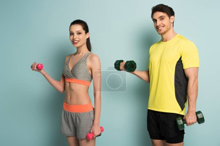 cheerful athletic couple training with dumbbells on blue