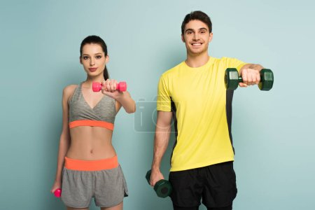 Photo for Beautiful happy athletic couple training with dumbbells on blue - Royalty Free Image