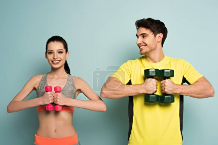 Photo for Smiling athletic couple holding dumbbells on blue - Royalty Free Image