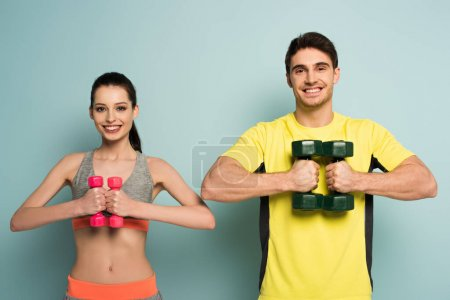 Photo for Cheerful sportive couple holding dumbbells on blue - Royalty Free Image