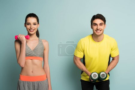 happy athletic couple training with dumbbells on blue
