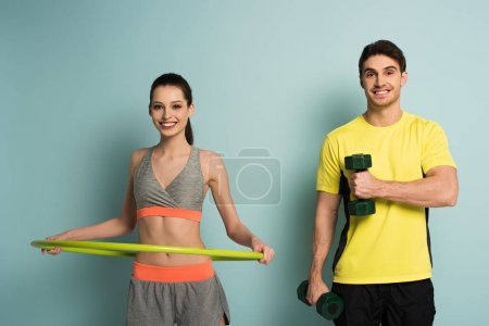 Photo for Cheerful athletic couple training with dumbbells and hula hoop on blue - Royalty Free Image