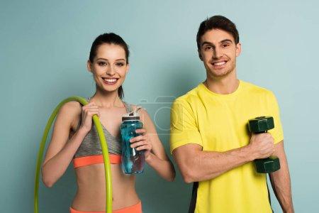 Photo pour Heureux couple athlétique tenant haltère, hula hoop et bouteille d'eau sur bleu - image libre de droit